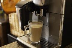 A máquina de café derrama o close-up fresco do café do cappuccino imagens de stock