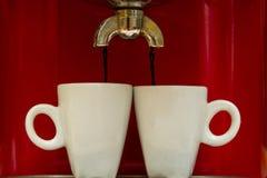 A máquina de café vermelha derrama o café em dois copos fotos de stock