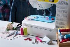 Máquina de coser con diversos accesorios en la tabla blanca Imagen de archivo libre de regalías