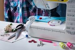 Máquina de coser con diversos accesorios en la tabla blanca Imágenes de archivo libres de regalías