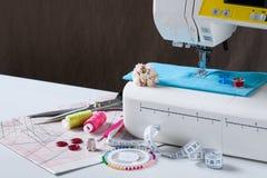 Máquina de coser con diversos accesorios en la tabla blanca Fotografía de archivo
