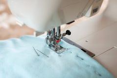 Máquina de coser, tela azul y pernos Imagen de archivo