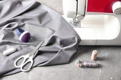 Máquina de coser, tela y accesorios para adaptar en la tabla Foto de archivo