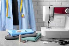 Máquina de coser, telas y accesorios para adaptar en la tabla Imagen de archivo