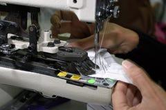 Máquina de coser y manos Imagenes de archivo