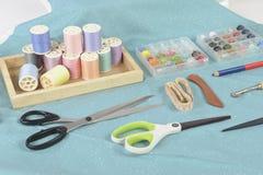 Máquina de coser y rollos del hilo, tijeras, tela y a coloridos Foto de archivo