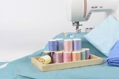 Máquina de coser y rollos del hilo, tijeras, tela y a coloridos Imágenes de archivo libres de regalías