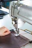 Máquina de costura com mãos da mulher imagens de stock
