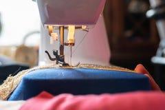Máquina de costura com um traje azul imagem de stock