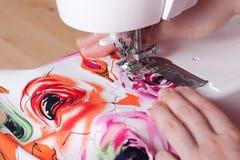 Mãos das mulheres com máquina de costura e matéria têxtil imagem de stock royalty free