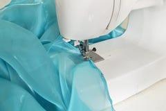 Máquina de costura Costura de um vestido ou de uma cortina azul à moda do tule Fotografia de Stock