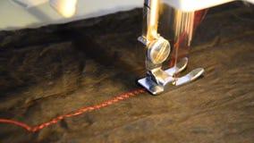 Máquina de costura e artigo da roupa preta com uma linha vermelha do contraste video estoque