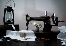 Máquina de costura manual do estilo retro clássico pronta para o trabalho, lâmpada de querosene Fotos de Stock