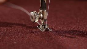Máquina de costura velha no pano vinous, fim acima, lento filme