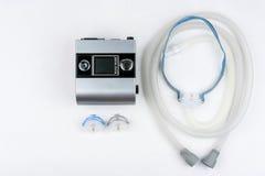 Máquina de CPAP con la manguera y máscara para la nariz Tratamiento para la gente con apnea de sueño Foto de archivo