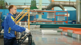 A máquina de dobra empurra as tubulações e o trabalhador toma e põe sobre a cremalheira filme