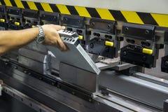 A máquina de dobra hidráulica do uso do operador do técnico foto de stock