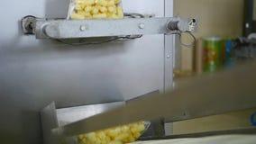A máquina de empacotamento na oficina do processo da fábrica do alimento de empacotar doces na folha empacota o operário Automate filme