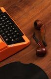 A máquina de escrever alaranjada do vintage na madeira Fotos de Stock