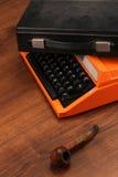 A máquina de escrever alaranjada do vintage na madeira Fotos de Stock Royalty Free