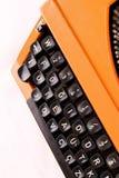 A máquina de escrever alaranjada do vintage no fundo branco Fotografia de Stock Royalty Free