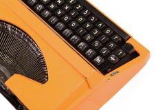 A máquina de escrever alaranjada do vintage no fundo branco Imagens de Stock Royalty Free