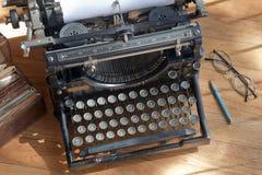 Máquina de escrever antiga velha em um contador de madeira Fotos de Stock