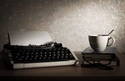Máquina de escrever com copo, livro e monóculos de café foto de stock royalty free