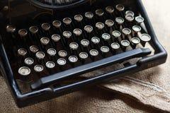 Máquina de escrever preta velha do vintage na tela de serapilheira Imagem de Stock Royalty Free