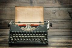 Máquina de escribir antigua con la página de papel llevada sucia en la tabla de madera Fotografía de archivo