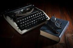 Máquina de escribir con el libro, las lentes y la pluma Fotos de archivo