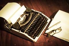 Máquina de escribir con el libro y las lentes Imagen de archivo libre de regalías