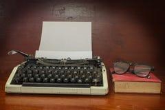Máquina de escribir con el libro y las lentes antiguos Fotografía de archivo libre de regalías