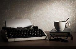 Máquina de escribir con la taza de café, el libro y las lentes Foto de archivo libre de regalías