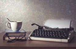 Máquina de escribir con la taza de café, el libro y las lentes, vintage filtrado Imagenes de archivo