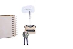 Máquina de escribir del hombre y un cuaderno espiral Imagen de archivo