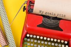 máquina de escribir roja con el texto ' Mis metas 2018' y documento de embalaje sobre fondo amarillo fotografía de archivo