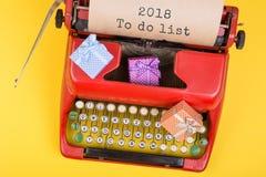 máquina de escribir roja con el texto ' 2018 para hacer list' y cajas de regalo en fondo amarillo imagen de archivo