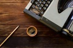 Máquina de escribir vieja con café en vieja textura de madera Fotografía de archivo libre de regalías