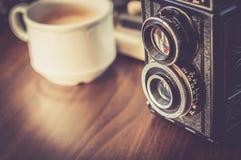Máquina de escribir vieja en la tabla de madera vieja con la cámara vieja del café Fotografía de archivo