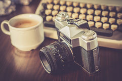 Máquina de escribir vieja en la tabla de madera vieja con la cámara vieja del café Imagenes de archivo