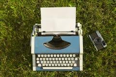 Máquina de escribir y cámara vieja en fondo de la hierba Fotos de archivo libres de regalías