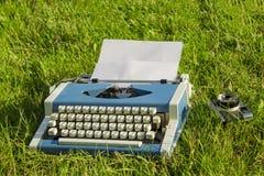 Máquina de escribir y cámara vieja en la hierba Fotografía de archivo libre de regalías