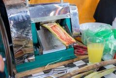 A máquina de espremedura para o suco da cana-de-açúcar fotos de stock royalty free