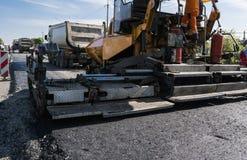 A máquina de funcionamento do paver do asfalto do trabalhador durante a construção de estradas e a reparação funciona Uma estação imagem de stock