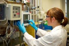 Máquina de funcionamiento de la mujer en laboratorio Imagen de archivo