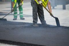 Máquina de funcionamiento de la pavimentadora del asfalto del trabajador Imagenes de archivo