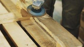 Máquina de la amoladora de ángulo del uso de la persona del carpintero a la estructura de madera lisa de las barras almacen de metraje de vídeo