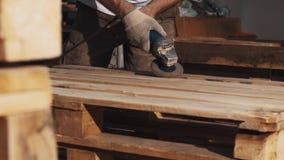 Máquina de la amoladora de ángulo del uso del hombre del carpintero a la estructura de madera lisa de las barras almacen de metraje de vídeo