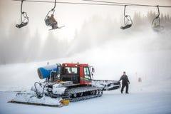 Máquina de la limpieza de la nieve que trabaja en cuesta del esquí debajo de sillas del cable Fotos de archivo libres de regalías